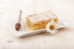 蜂蜜梳子和春黄菊花 免版税库存照片