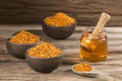 蜂蜜玻璃瓶子和花粉-顶视图 免版税库存照片