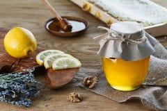 蜂蜜瓶子和柠檬片 免版税图库摄影