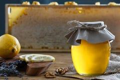 蜂蜜瓶子和柠檬片 免版税库存图片