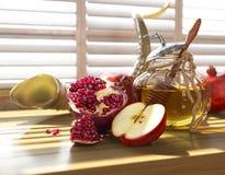 蜂蜜瓶子用苹果和石榴为犹太新年假日 库存照片