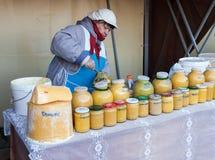 蜂蜜的妇女卖主在传统市场上的 免版税图库摄影