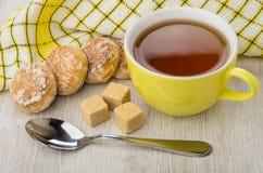 蜂蜜蛋糕、多块的糖、茶匙、餐巾和茶 库存图片