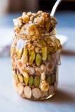 蜂蜜风味坚果、杏仁和花生糖点心在瓶子 图库摄影