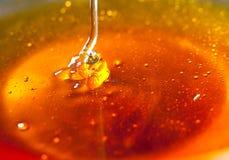 蜂蜜水滴到bowl.JH里 免版税库存图片