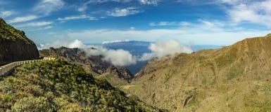蜒蜒路和天空蔚蓝,拉戈梅拉,山风景海岛令人惊讶的看法与美丽的蓬松云彩的  好日子 免版税库存照片