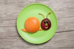 蜗牛做用果子在板材和桌 免版税图库摄影