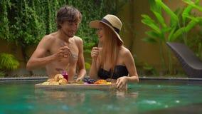 蜜月游人一对年轻夫妇吃他们在一张浮动桌上的自己的个人早餐在一私有游泳场 影视素材
