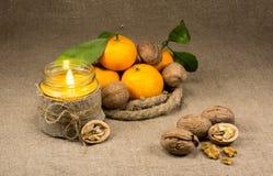 蜜桔、坚果和一个蜡烛 库存照片
