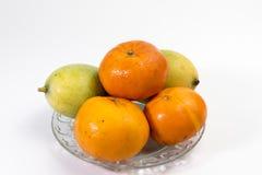 蜜桔和芒果在一块玻璃板 免版税库存照片