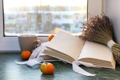 蜜桔和葡萄酒在一张大理石桌上预定由窗口 免版税库存图片