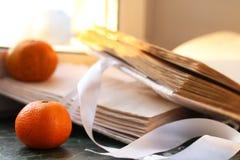 蜜桔和葡萄酒在一张大理石桌上预定由窗口 免版税图库摄影
