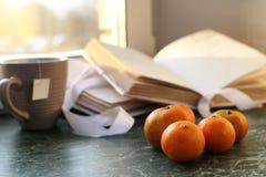 蜜桔和葡萄酒在一张大理石桌上预定由窗口 库存图片
