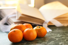 蜜桔和葡萄酒在一张大理石桌上预定由窗口 库存照片