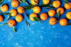 蜜桔或普通话与绿色叶子在土气蓝色桌上在舱内甲板从上面放置样式 免版税库存图片