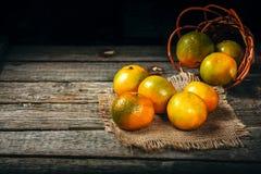 蜜桔普通话,柑桔,与叶子的柑橘水果在与拷贝空间的土气木背景 免版税库存图片