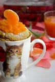 蜜桔松饼在一个白色杯子的一个微波炉烹调了有小猫的图片的 免版税图库摄影