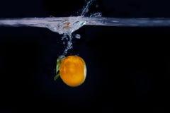 蜜桔飞溅在水中 概念威胁域生气勃勃冰箱里面 库存图片