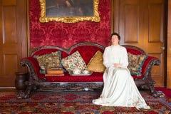 蜡夫人坐红色沙发 免版税库存图片