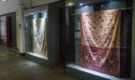 蜡染布在有在蜡染布博物馆拍的照明设备照片的玻璃门橱柜显示的织品收藏北加浪岸印度尼西亚 免版税库存照片