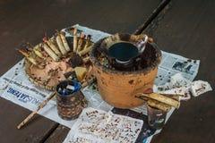 蜡染布工具,倾斜和热的蜡在木桌顶部处理照片的蜡染布的拍在北加浪岸印度尼西亚 免版税库存图片