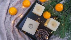 蜡烛、橙色蜜桔、杉木锥体在黑盘子和舒适彩色小灯在knitte格子花呢披肩backgroundand 圣诞节装饰生态学木 免版税库存照片