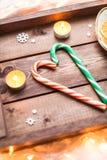 蜡烛、糖果和桔子在圣诞节木盘子 免版税库存照片