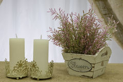蜡烛和一箱人造花 免版税库存照片