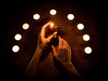 蜡烛和女性手有锋利的钉子的 占卜和巫术,低调 免版税库存图片