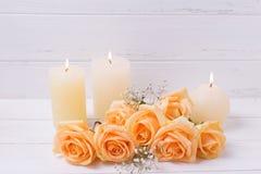 蜡烛和桃子上色在白色木backgroun的玫瑰花 免版税库存图片
