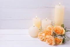蜡烛和桃子上色在白色木backgroun的玫瑰花 库存图片