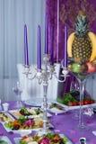 蜡烛和盘在桌上 浪漫片剂 用婚礼celebr的蜡烛服务与鲜美盘和装饰的表 免版税库存图片