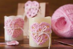 蜡烛和礼物包裹的手工制造钩针编织桃红色心脏Sain的 库存照片