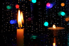 蜡烛在与雨下落的一个窗口前面站立 免版税库存照片