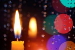 蜡烛在与雨下落的一个窗口前面站立 免版税库存图片
