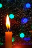 蜡烛在与雨下落的一个窗口前面站立 图库摄影