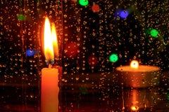 蜡烛在与雨下落的一个窗口前面站立 免版税图库摄影
