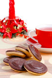 蜡烛巧克力曲奇饼托起红色茶 库存照片