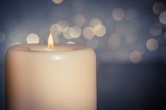 蜡烛特写镜头与火焰的在蓝色bokeh背景的木桌上 免版税库存图片