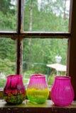 蜡烛的三个玻璃杯子在窗口前面 库存图片
