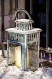 蜡烛的被冰的灯笼在金属前沿栏杆前面 免版税库存照片