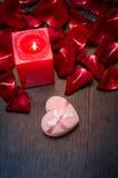 蜡烛,红色瓣上升了与在桌上的礼物盒 在红色玫瑰色华伦泰白色的概念重点 免版税库存图片