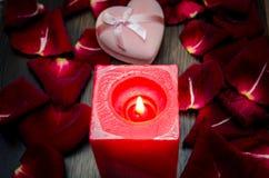 蜡烛,红色瓣上升了与在桌上的礼物盒 图库摄影