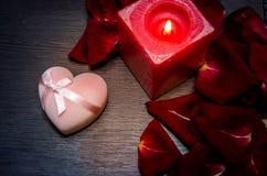 蜡烛,红色瓣上升了与在桌上的礼物盒 库存图片