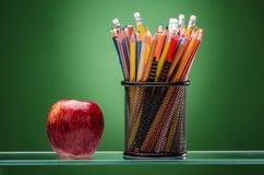 蜡笔、标志和红色苹果 免版税库存照片