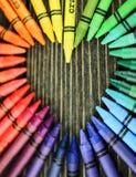 从蜡笔的心脏在桌上 免版税库存图片