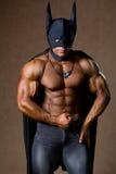 蝙蝠侠服装的一个肌肉人。 库存图片
