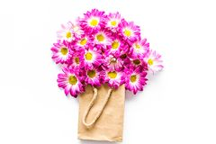 蝴蝶下落花卉花重点模式黄色 在一个纸袋的花束在白色背景顶视图copyspace 库存照片