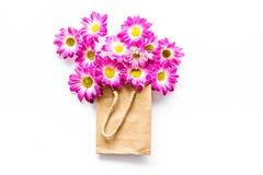 蝴蝶下落花卉花重点模式黄色 在一个纸袋的花束在白色背景顶视图copyspace 库存图片
