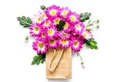 蝴蝶下落花卉花重点模式黄色 在一个纸袋的花束在白色背景顶视图copyspace 图库摄影